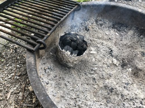 charcoal in chimney in firepit with grate