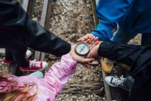 four kids holding a compass