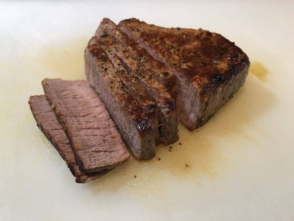 steak on cutting board, partially sliced