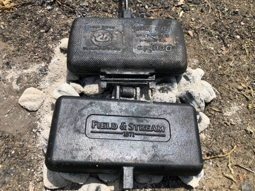 two double pie irons resting on coals