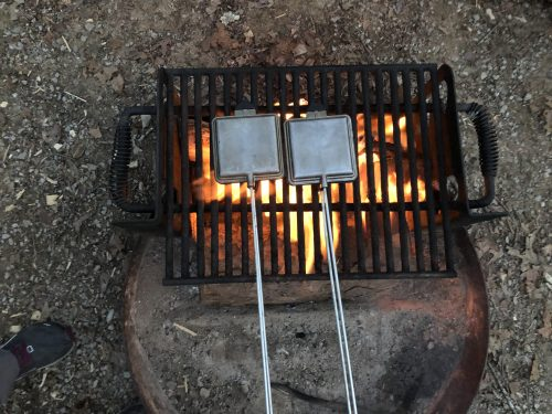 square pie irons on grate over fire