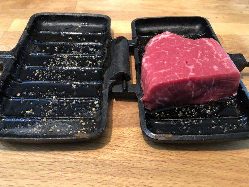 double pie iron showing uncooked steak