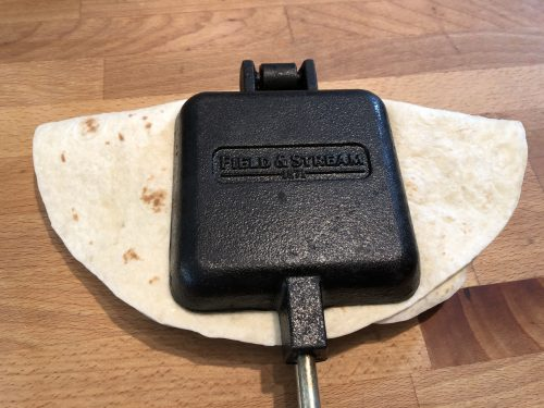 pie iron closed with tortilla sticking out