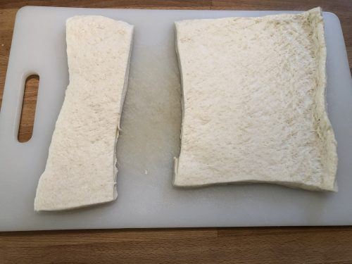pizza dough cut to size on cutting board