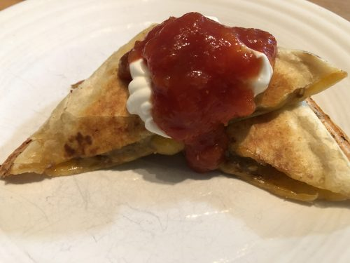 pie iron tasty taco with sour cream and salsa on a white plate