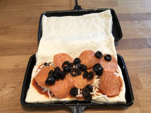 toppings added to pizza dough in pie iron