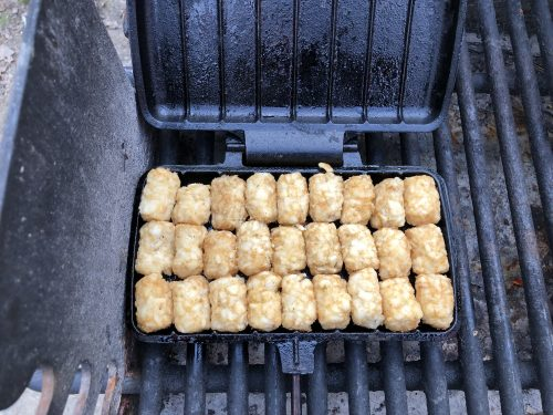 tator tots lined up in pie iron on grill