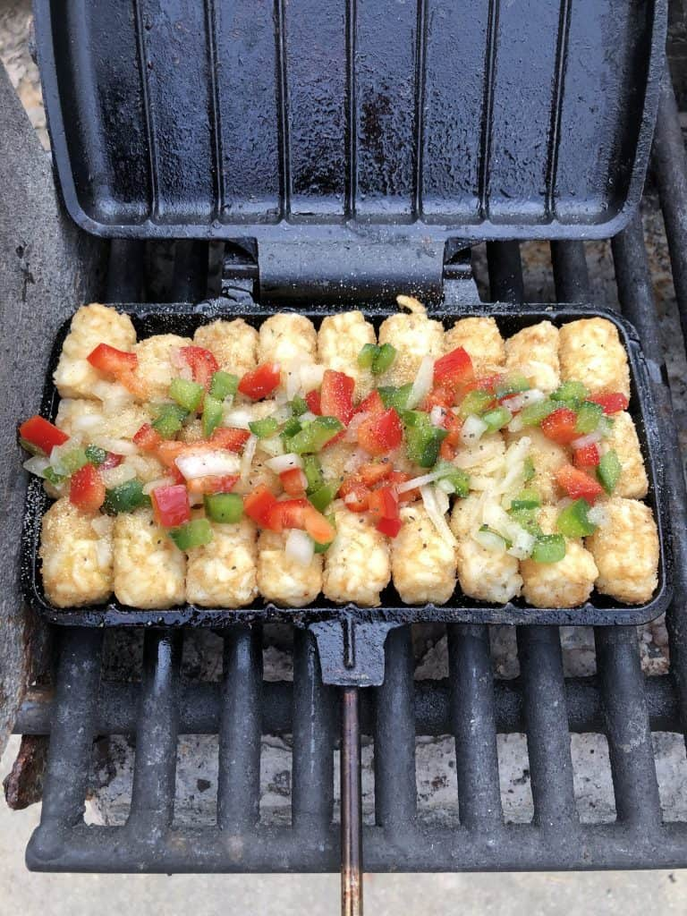 tator tots with peppers and onions in pie iron on grill