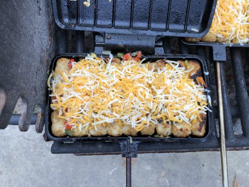cheese covering cooked tator tots with peppers and onions in pie iron on a grill