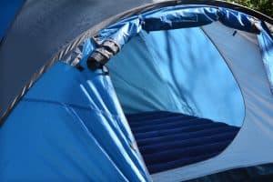 blue air mattress inside blue tent with door open