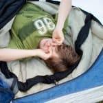 kid in sleeping bag inside of tent waking up