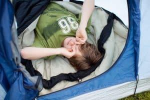 kid in sleeping bag inside tent waking up