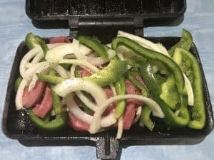 peppers onions and steak in pie iron for grilling