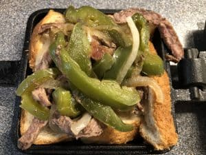 slice of bread with cooked steak peppers and onions in pie iron