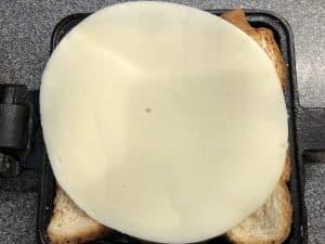 slice of bread with provolone cheese in pie iron