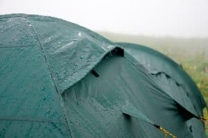 camping in the rain in a green tent