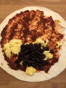 scrambled eggs and beans on tortilla with chipotle peppers