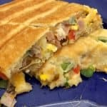 ham and cheese omelet baked in crescent dough cooked in a pie iron plated on blue