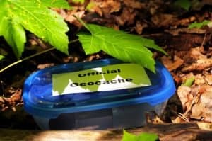 blue lidded container with words Official Geocache hidden in leaves