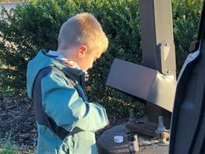 kid finding a small geocache under the skirt of a lamp pole