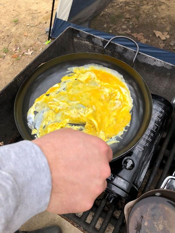 eggs being scrambled on a camping stove