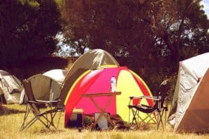 accessory table for camping in front of red and yellow tent
