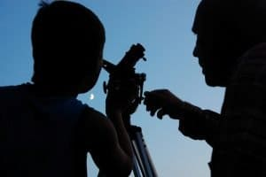 Adult and child looking at moon through telescope
