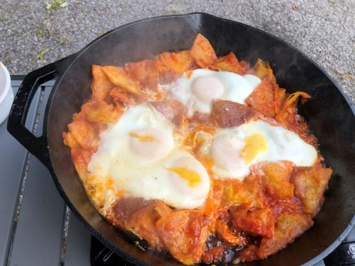 four over easy eggs sitting on top of fried tortillas in red sauce in a cast iron skillet