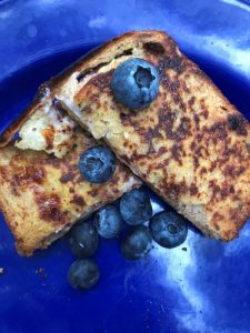 Pie Iron Cream Cheese French Toast with blueberries on blue plate
