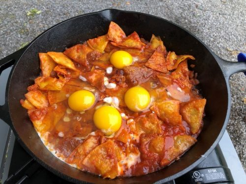 four eggs sitting on top of fried tortillas in red sauce