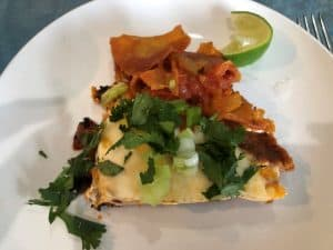 chilaquiles with egg, cilantro, lime slice on a white plate