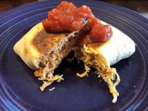 chicken chimichanga cooked in a camp cooker on a plate with salsa