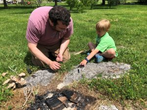 adult and child using rod to make sparks for fire