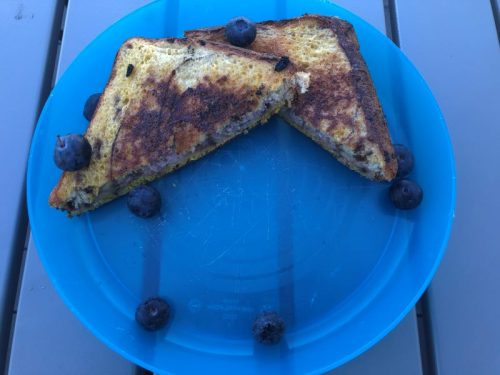 Pie Iron Cream Cheese French Toast ready to eat on blue plate with blueberries
