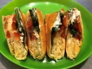 spinach & red bell pepper strips with cream cheese in crescent roll dough on green plate