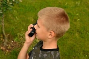 blond boy on walkie talkie while camping in green field